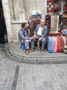 HOW BAZAAR Two vendors at the Grand Bazaar take a moment's break. A young boy bearing a tea tray soon served them refreshments right there on the pavement